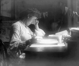 Historical image of woman writing, from glass plate photo.